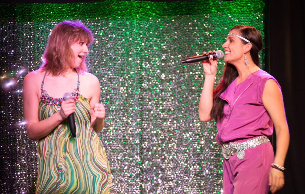 Johanna und Verena tanzen und singen sich in flippigen Outfits durch die Musik Geschichte