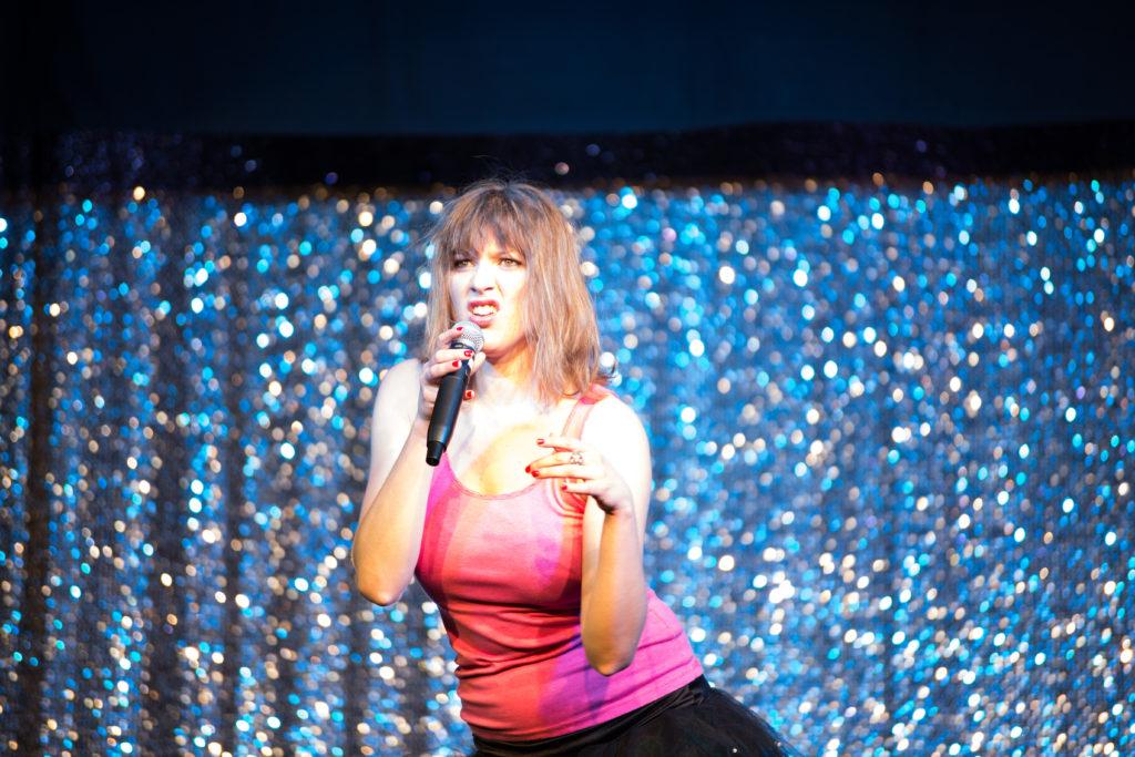 Johanna singt in einer provokanten Pose auf der Bühne